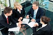 4 אנשים עסקים יושבים סביב שולחן